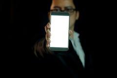 Το άτομο στο σκοτάδι παρουσιάζει έξυπνο τηλέφωνο στοκ εικόνες