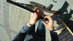 Το άτομο συγκεντρώνει Submachine το πυροβόλο όπλο στην τετραγωνική τοπ άποψη λεωφόρων φιλμ μικρού μήκους