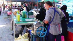 Το άτομο συμπιέζει το χυμό από τους μίσχους καλάμων στην αγορά στην πόλη Kamala Ταϊλάνδη φιλμ μικρού μήκους