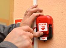 Το άτομο συνδέει το κουμπί της πυρκαγιάς που προειδοποιεί με έναν τοίχο δωματίων Το ρωσικό κείμενο - η πυρκαγιά Μετατόπιση κάτω στοκ φωτογραφία