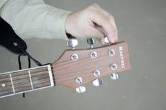 Το άτομο συντονίζει τους συντονίζοντας γόμφους σε μια κιθάρα του Martinez σε ένα γκρίζο υπόβαθρο στοκ εικόνες με δικαίωμα ελεύθερης χρήσης