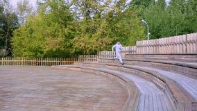 Το άτομο συσσωρεύει ένα σύνολο σκαλοπατιών στο πάρκο Άτομο που τα σκαλοπάτια στο πάρκο φιλμ μικρού μήκους