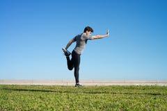 Το άτομο τεντώνει το σώμα πρίν τρέχει Στοκ εικόνα με δικαίωμα ελεύθερης χρήσης