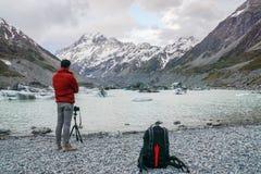 Το άτομο τουριστών με το σακάκι παίρνει τη φωτογραφία του υποστηρίγματος Cook από DSLR τη κάμερα με το τρίποδο στοκ εικόνες με δικαίωμα ελεύθερης χρήσης