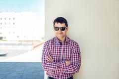 Το άτομο το καλοκαίρι ενάντια στον τοίχο, γυαλιά, ευτυχή χαμόγελα, που φορά τα τζιν και ένα πουκάμισο, φωτεινή ηλιόλουστη ημέρα Η Στοκ φωτογραφία με δικαίωμα ελεύθερης χρήσης