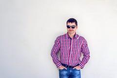 Το άτομο το καλοκαίρι ενάντια στον τοίχο, γυαλιά, σοβαρά βλέμματα στο μέτωπο, στα τζιν και ένα πουκάμισο, τη φωτεινή ηλιόλουστη η Στοκ φωτογραφία με δικαίωμα ελεύθερης χρήσης