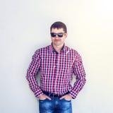 Το άτομο το καλοκαίρι ενάντια στον τοίχο, γυαλιά, σοβαρά βλέμματα στο μέτωπο, στα τζιν και ένα πουκάμισο, τη φωτεινή ηλιόλουστη η Στοκ εικόνες με δικαίωμα ελεύθερης χρήσης