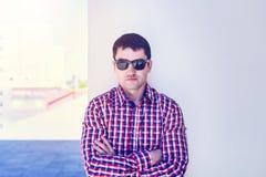 Το άτομο το καλοκαίρι ενάντια στον τοίχο, τα γυαλιά, το σοβαρό Διευθύνον Σύμβουλο, στα τζιν και ένα πουκάμισο, έξυπνο τον ηλιόλου Στοκ Φωτογραφία