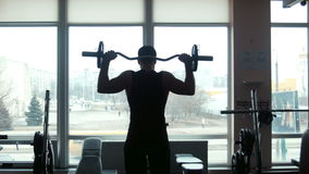 Το άτομο το weightlifter ανυψώνει ένα barbell σε μια γυμναστική απόθεμα βίντεο