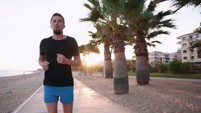 Το άτομο τρέχει μόνο στο χρόνο ηλιοβασιλέματος στο γραφικό ανάχωμα πόλεων, μετωπική άποψη φιλμ μικρού μήκους