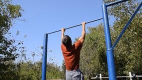 Το άτομο τραβιέται επάνω στο φραγμό Αθλητισμός παιχνιδιού στο καθαρό αέρα Σπιτικός οριζόντιος φραγμός στο κατώφλι απόθεμα βίντεο