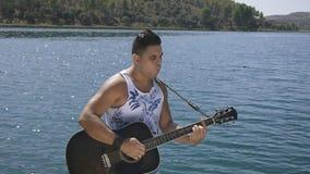 Το άτομο τραγουδά ένα τραγούδι με μια κιθάρα φιλμ μικρού μήκους