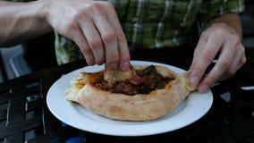 Το άτομο τρώει ένα εθνικό της Γεωργίας πιάτο - khachapuri, μετακίνηση καμερών Ο τύπος διακόπτει ένα κομμάτι του ψωμιού και της βύ απόθεμα βίντεο