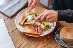 Το άτομο τρώει Μαχαίρι και δίκρανο διαθέσιμα πίνακας προγευμάτων Αμερικανικό πρόγευμα ύφους με τα τηγανισμένα αυγά, λουκάνικο, πρ στοκ φωτογραφίες με δικαίωμα ελεύθερης χρήσης