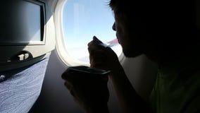 Το άτομο τρώει τα τρόφιμα με ένα δίκρανο καθμένος από ένα παράθυρο σε ένα αεροπλάνο κατά την πτήση απόθεμα βίντεο