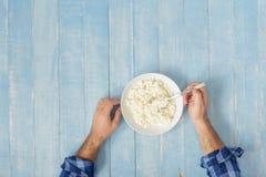 Το άτομο τρώει το τυρί εξοχικών σπιτιών, τοπ άποψη πρόγευμα υγιές Στοκ Φωτογραφία
