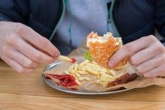 Το άτομο τρώει burger σε έναν γευματίζοντα οδών γρήγορου γεύματος Στοκ Φωτογραφίες