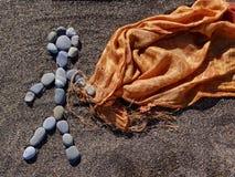 Το άτομο των πετρών κρατά το ύφασμα στην άμμο Στοκ Εικόνα