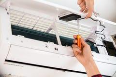 Το άτομο υπηρεσιών είναι συντήρηση του κλιματιστικού μηχανήματος στοκ φωτογραφία με δικαίωμα ελεύθερης χρήσης