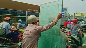 Το άτομο φέρνει τα μεγάλα κομμάτια γυαλιού στο μηχανικό δίκυκλο στην οδό κυκλοφορίας απόθεμα βίντεο