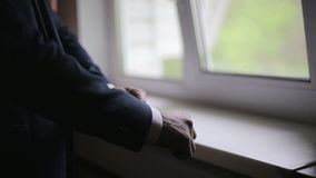Το άτομο φορά ένα σακάκι στα ξημερώματα στο σκοτεινό δωμάτιο απόθεμα βίντεο