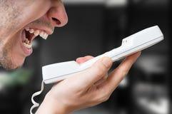 Το άτομο φωνάζει στο τηλέφωνο στοκ εικόνες