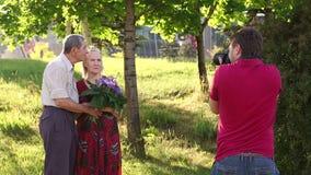 Το άτομο φωτογραφίζει ένα ηλικιωμένο ζεύγος στο πάρκο απόθεμα βίντεο