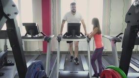 Το άτομο χάνει το βάρος treadmill στη γυμναστική με τον προσωπικό εκπαιδευτή Υγεία και ικανότητα Προθέρμανση πριν από τις ασκήσει φιλμ μικρού μήκους