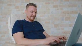 Το άτομο χαμογελά εύκολα και αντιστοιχεί με κάποιο στο lap-top απόθεμα βίντεο