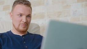 Το άτομο χαμογελά εύκολα και εργάζεται πίσω από το lap-top απόθεμα βίντεο