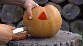 Το άτομο χαράζει από μια κολοκύθα Jack-ο ` - φανάρι στο κατώφλι σε ένα κολόβωμα δέντρων απόθεμα βίντεο