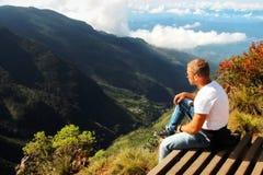 Το άτομο χαλαρώνει στην άκρη του απότομου βράχου Τέλος οροπέδιων ` του κόσμου `, Σρι Λάνκα Στοκ Φωτογραφίες