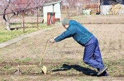 Το άτομο χαλαρώνει το έδαφος χρησιμοποιώντας ένα άροτρο Στοκ Φωτογραφία