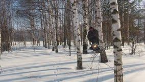 Το άτομο το χειμώνα ντύνει γρήγορα να οδηγήσει στο μίνι όχημα για το χιόνι βαθιά snowdrifts στο δάσος και τον ελιγμό μεταξύ των δ απόθεμα βίντεο