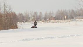 Το άτομο το χειμώνα ντύνει την οδήγηση στο μίνι όχημα για το χιόνι βαθιά snowdrifts στον τομέα, που περπατά με το χιόνι και που κ φιλμ μικρού μήκους