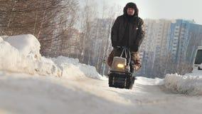 Το άτομο το χειμώνα ντύνει την οδήγηση στο μίνι όχημα για το χιόνι με ένα ρυμουλκό και έναν επιβάτη σε έναν χειμερινό δρόμο φιλμ μικρού μήκους