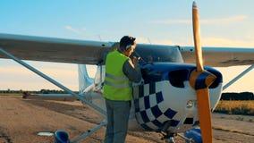 Το άτομο χρησιμοποιεί το ειδικό ραβδί για να ελέγξει ένα επίπεδο πετρελαίου μηχανών σε ένα αεροπλάνο απόθεμα βίντεο