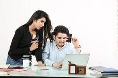Το άτομο χρησιμοποιεί το lap-top και το κορίτσι φαίνεται εργασία στο lap-top Στοκ Φωτογραφία