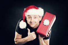 Το άτομο Χριστουγέννων που παρουσιάζει τον αντίχειρα υπογράφει επάνω και κιβώτιο δώρων Στοκ Εικόνες