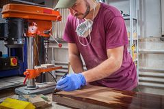 Το άτομο χρωματίζει έναν ξύλινο Στοκ Εικόνες