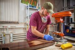 Το άτομο χρωματίζει έναν ξύλινο Στοκ Εικόνα