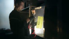 Το άτομο χρωματίζει τη λεπτομέρεια στο κίτρινο χρώμα από το πυροβόλο όπλο ψεκασμού στην κουκούλα εξάτμισης, χρωματισμός εργοστασί απόθεμα βίντεο