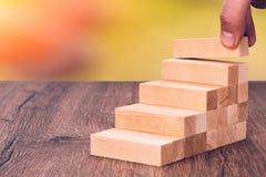 Το άτομο χτίζει μια ξύλινη σκάλα Έννοια: σταθερή ανάπτυξη στοκ φωτογραφίες