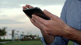 Το άτομο χτυπά σε μια ψηφιακή ταμπλέτα στο ηλιοβασίλεμα στοκ φωτογραφία