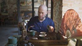 Το άτομο χύνει το ζεστό νερό σε μια κατσαρόλα Κινεζική τελετή τσαγιού απόθεμα βίντεο