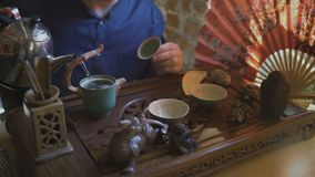 Το άτομο χύνει το ζεστό νερό σε μια κατσαρόλα Κινεζική τελετή τσαγιού φιλμ μικρού μήκους