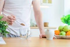 Το άτομο χύνει το στιγμιαίο καφέ σε ένα φλυτζάνι στην κουζίνα Έννοια καφέ ή προγευμάτων πρωινού στοκ φωτογραφίες