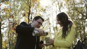 Το άτομο χύνει στο παγωμένο κορίτσι το ζεστό ποτό από thermos φιλμ μικρού μήκους