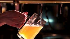 Το άτομο χύνει την μπύρα σε ένα ποτήρι απόθεμα βίντεο