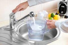 Το άτομο χύνει το νερό στην κανάτα φίλτρων στοκ φωτογραφίες